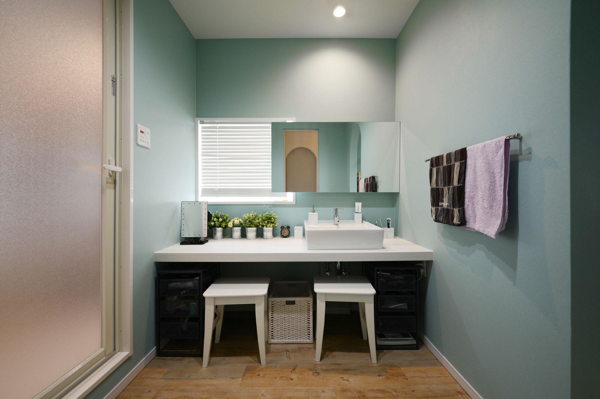 洗面台横の化粧スペースは、自然光を使える工夫も。の写真