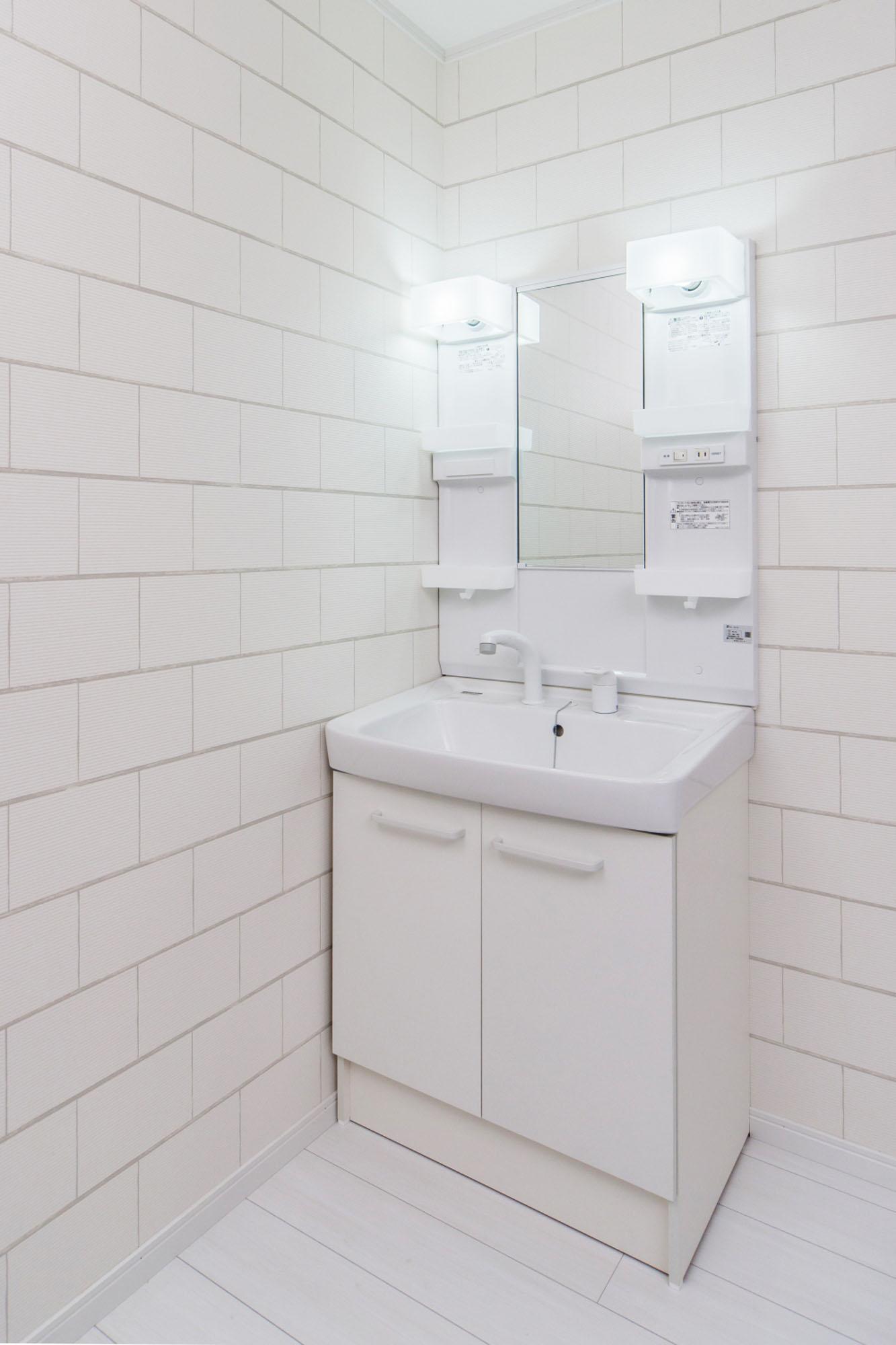 白いタイルの洗面。の写真