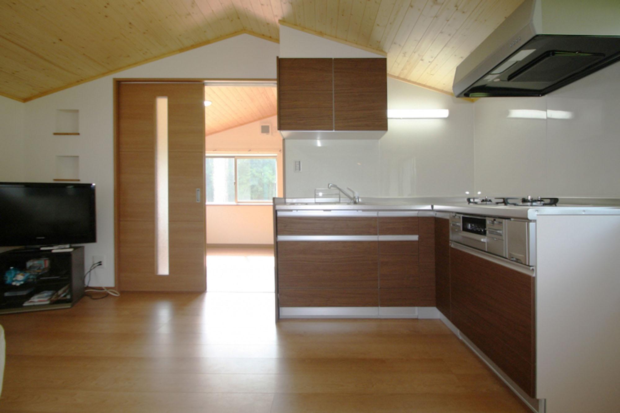 床と天井の色に合わせたキッチン。の写真