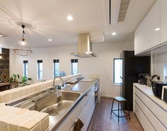 ステンレスのキッチンは自然石風のタイルともマッチ。の写真
