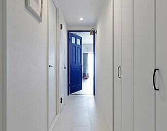 白いフロアタイルの廊下の先、青いドアがアクセント。の写真