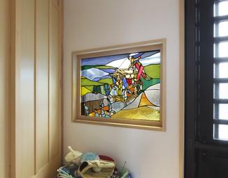 町の文化を描いたステンドグラスを玄関に。の写真