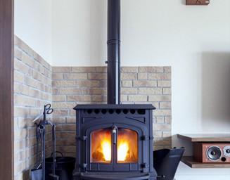 ペレットストーブまわりは、耐熱性の高い外壁タイルで。の写真