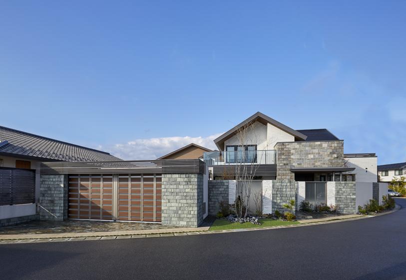 住宅と同形状・同色の横格子をカーポート上部に使用し、一体感を醸成。外壁タイルも住宅に合わせるなどして風格を打ち出しています。の写真