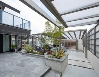 隣家との境の半透明パネルが明るさとプライバシーを確保。テラスからバルコニーへの空間には、広々とした抜け感が。の写真