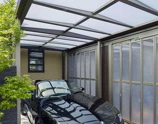 半透明のパネルの屋根から射す光が、車をより美しく見せてくれるカーポート。の写真