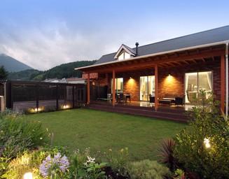 家の前には青々とした芝生と色とりどりの花が広がります。の写真