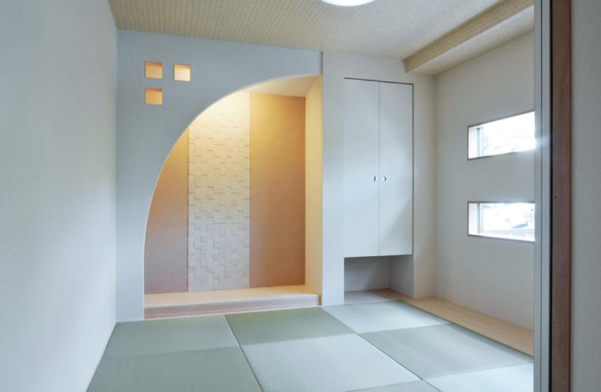 曲線の壁を用いた床の間にはエコカラットと間接照明。の写真
