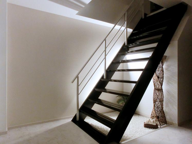 玄関ホールから居住スペースに行く階段。の写真
