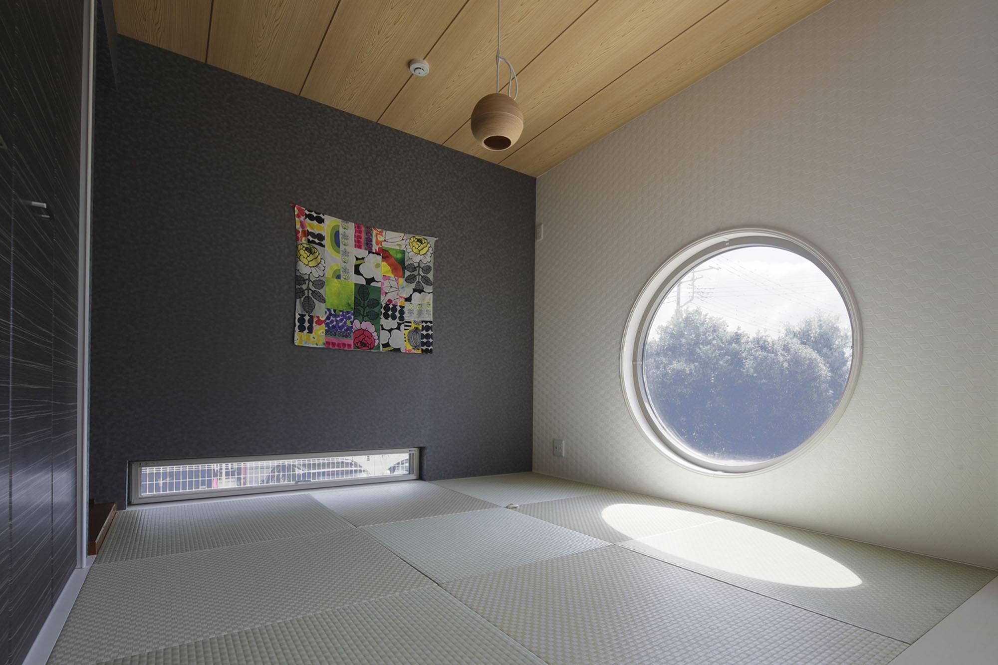 大きな丸い窓の和室。の写真